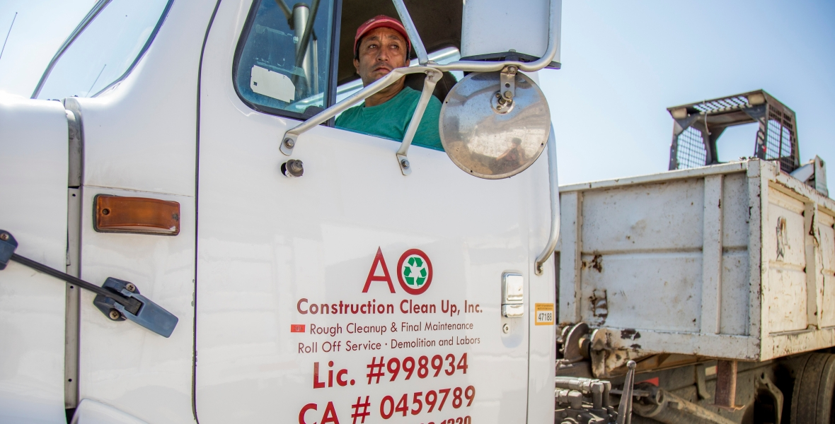 Antonio Ornelal driving his roll-off dumpster truck to his next rental for junk removal.