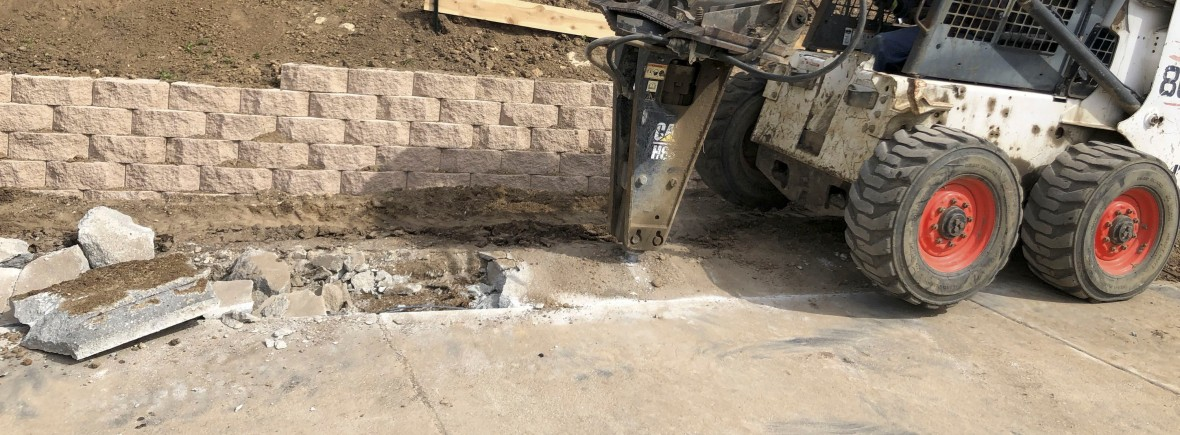 Concrete removal project in progress with bobcat tractor